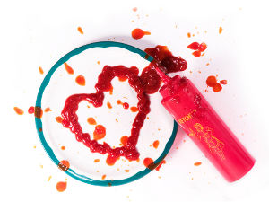 ketchup squeeze bottle that has drawn a messy heart of a plate