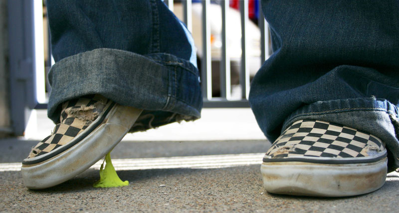 shoe lifting from ground with green chewing gum sticking to it and the pavement