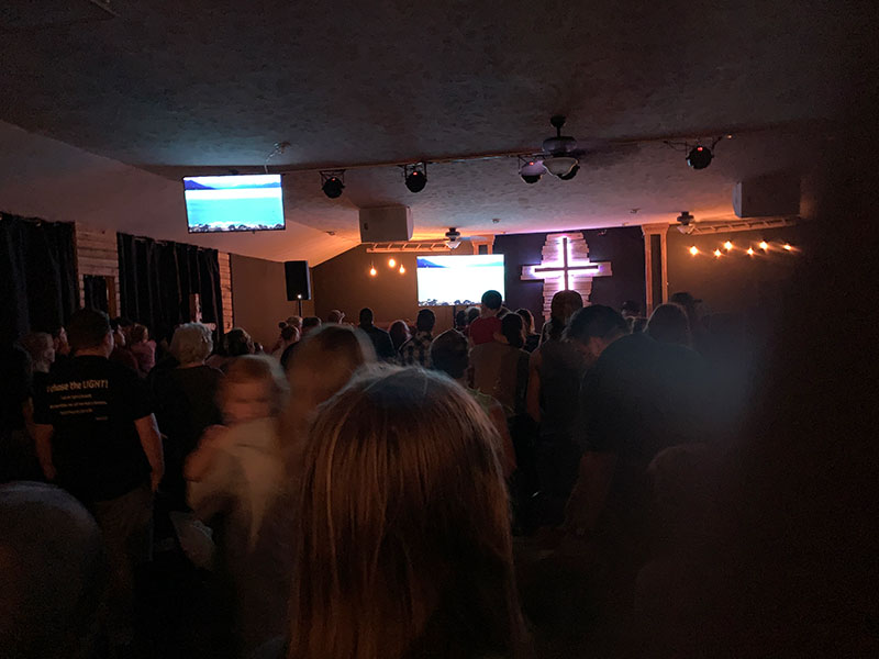 Dimmly lit sanctuary with monitors displaying background images as people stand in worship at Renovation Church in Mansfield, Missouri